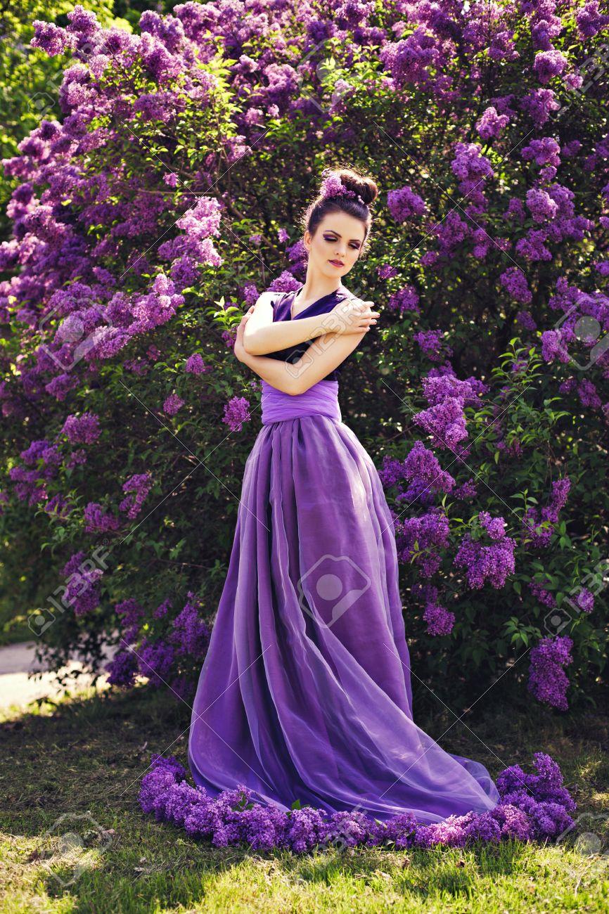 Hermosa Niña De Vestido Lila Bola Entre Las Flores En El Jardín