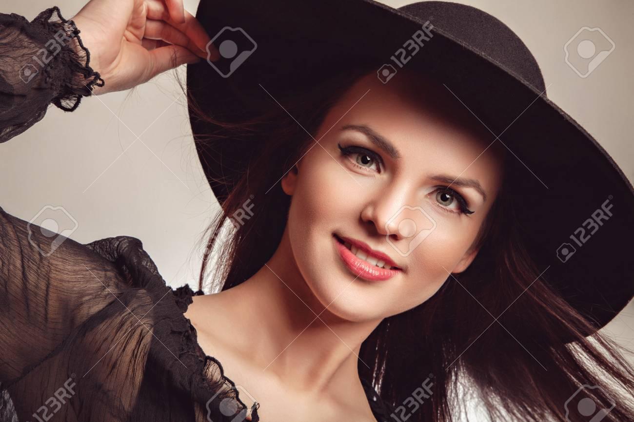 f159cd3e137c Archivio Fotografico - Bella giovane donna bruna alla moda con i capelli  lunghi in posa in abito nero e cappello nero. Stile Vogue. Foto dello studio
