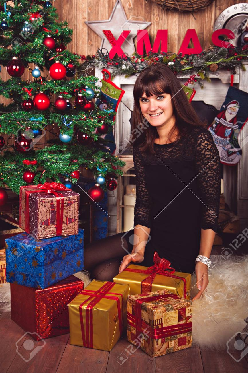 stock photo young woman in elegant lace dress with christmas gifts in the cozy home atmosphere before the christmas tree and fireplace studio photo