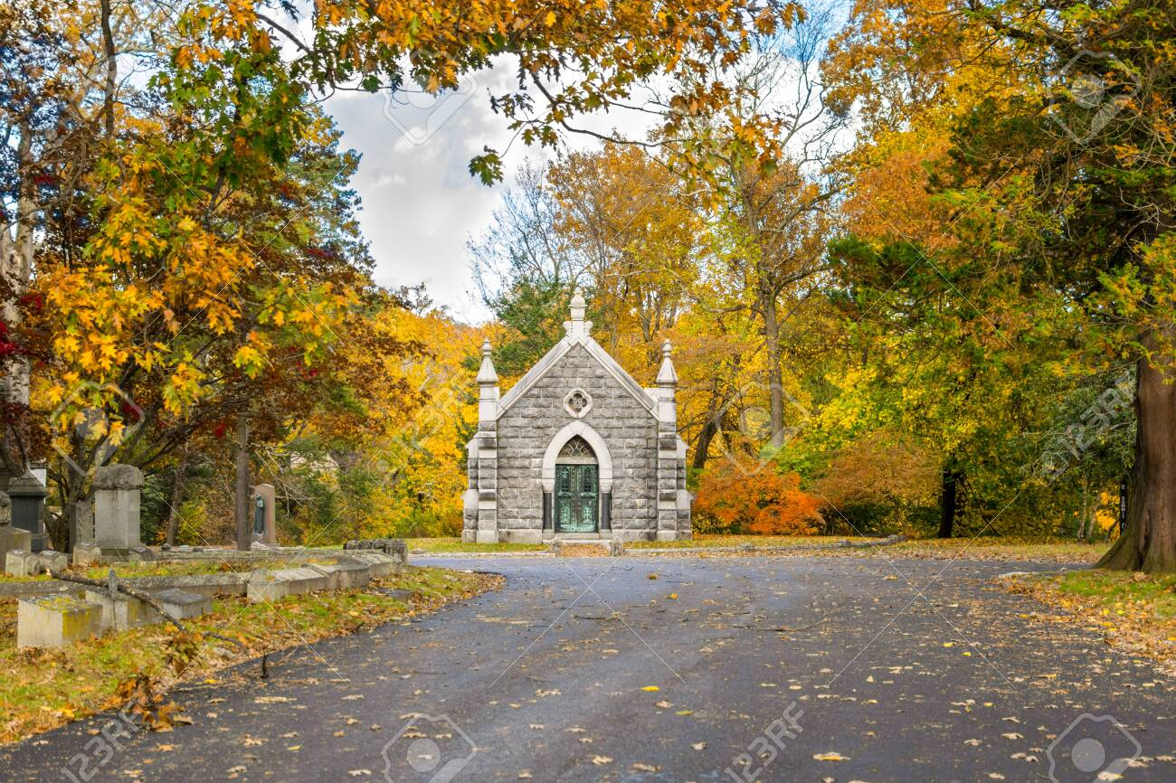 Small mausoleum at Sleepy Hollow Cemetery surrounded by autumnal fall foliage, Upstate New York, NY, USA - 120964337