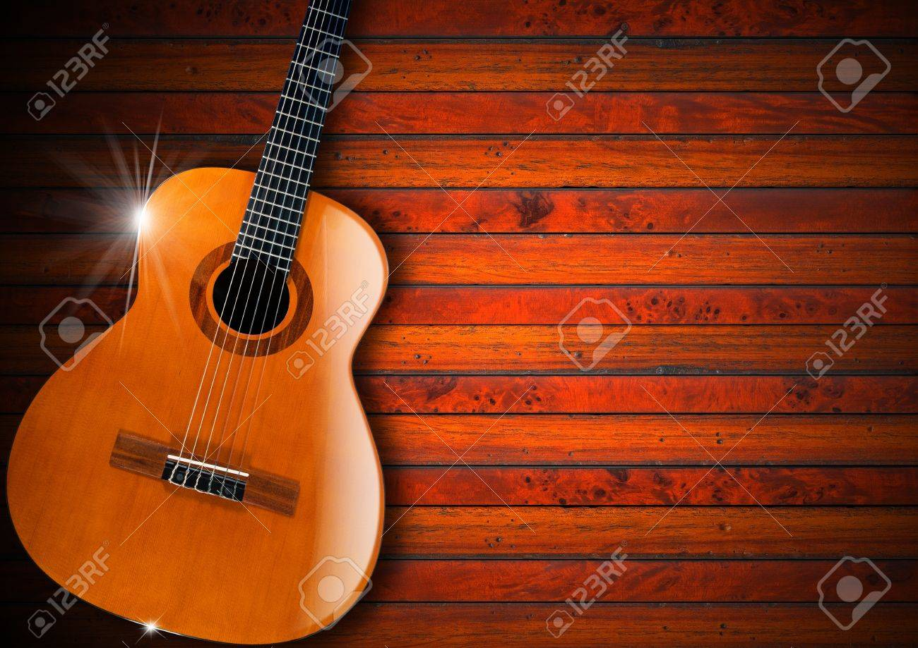 Acoustic Brown Guitar Against A Rustic Wood Background Stock Photo
