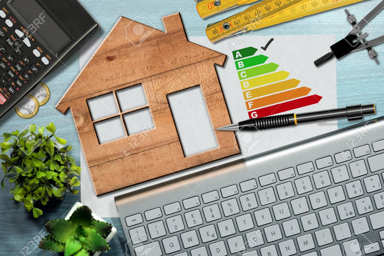 Energy efficiency rating graph on a desk with a wooden house model, calculator, folding ruler, drawing compass, pencil and a computer keyboard - 87941847