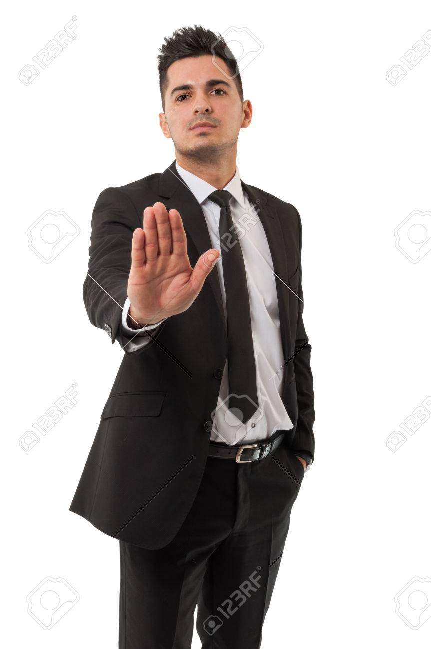 Business man wearing a classic black suit is saying stay right there by using his right hand - 26582850