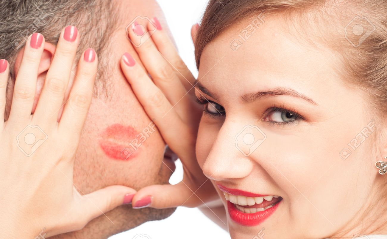 Beautiful woman framing lipstick kiss on a man face - 32754514