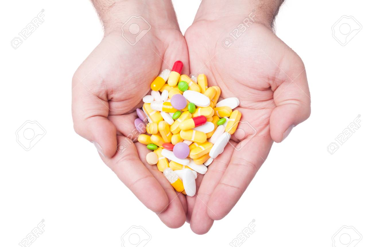 A man is holding a lot of different pills in both his hands - 35478108