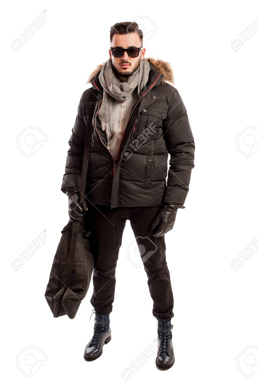 fashionable male model wearing winter clothes and a big bag on