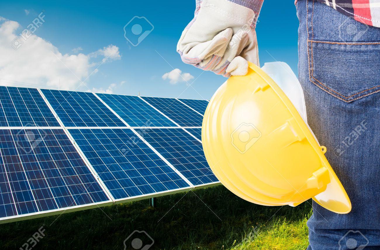 Engineer holding yellow construction helmet on solar power panels background - 43003658