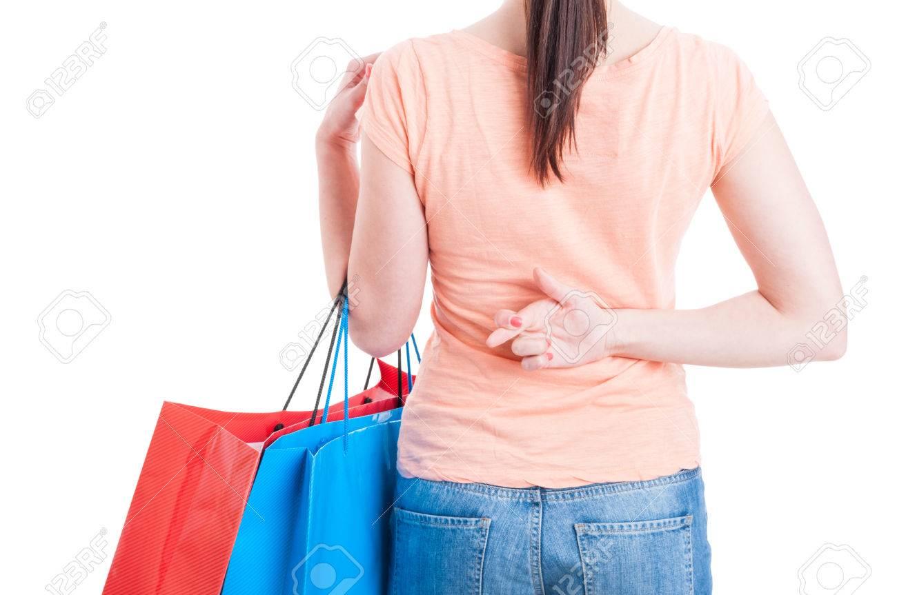 Bolsas de la compra mujer que sostienen que muestran los dedos cruzados detrás de la espalda gesto aislado en el fondo blanco con el espacio de la