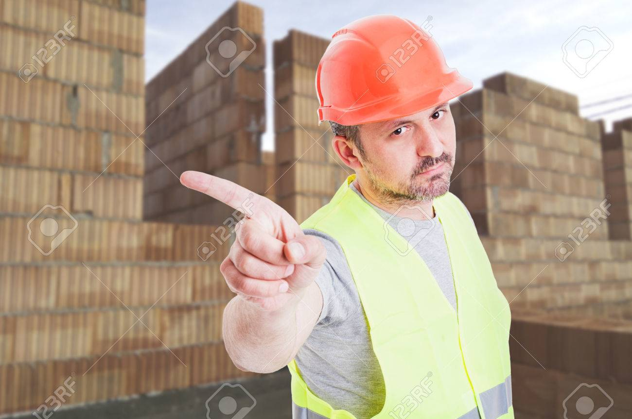 Serious builder in protection equipment doing a refusal gesture while standing on construction site - 66397935