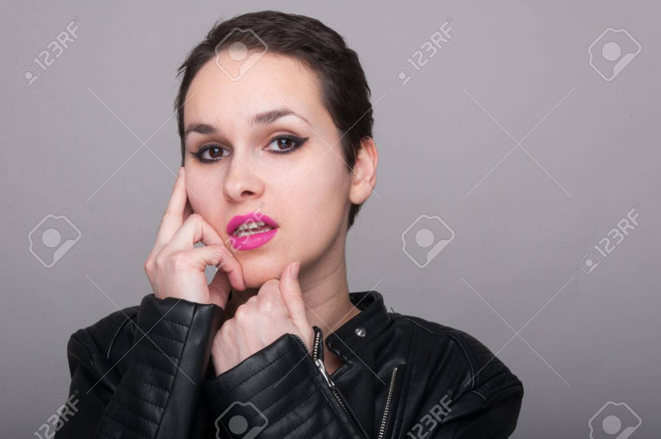 5c721a0db Punk girl dressed in leather jacket touching her face with fingers on gray  studio background with
