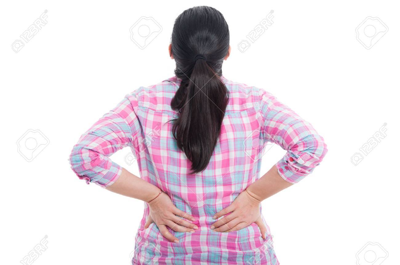 Rear view of a female with lower back pain holding hands to her spine on white background - 74188372