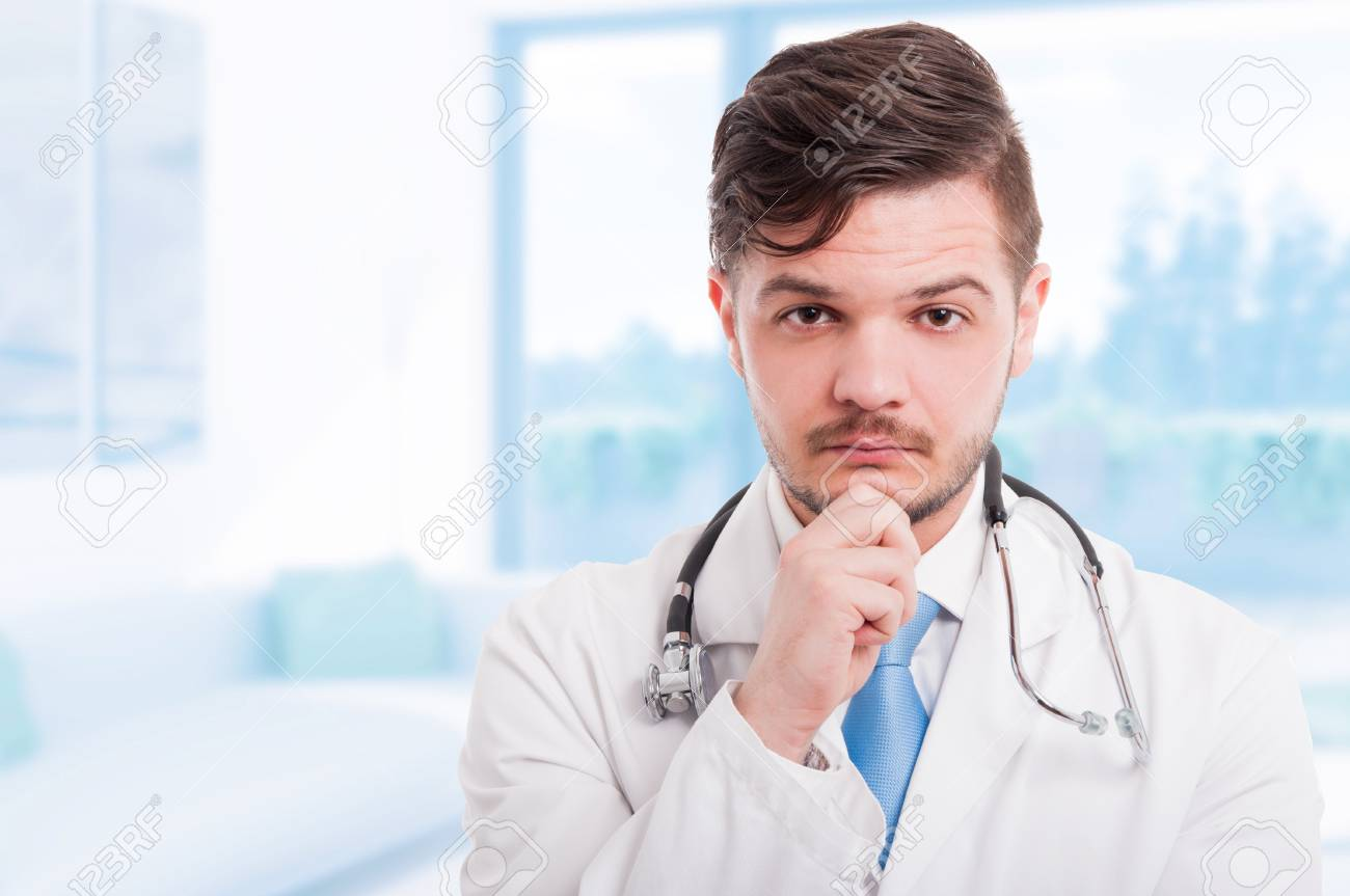 Portrait of handsome pensive doctor in white coat keeping hand on his chin and thinking with copy space - 75228017