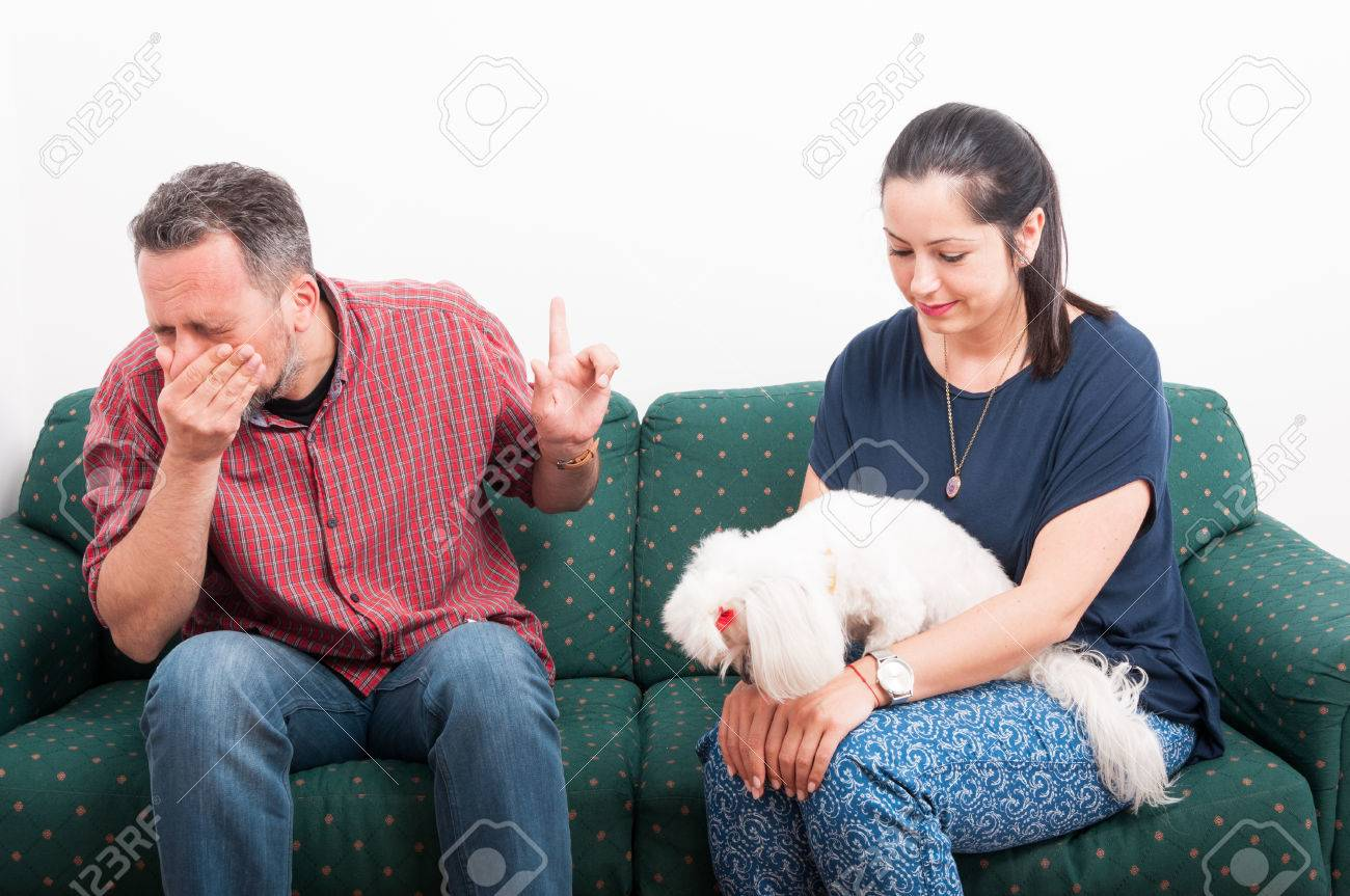 Young male sneezing while talking to his girlfriend on the sofa as allergy or sickness symptom concept - 76952046