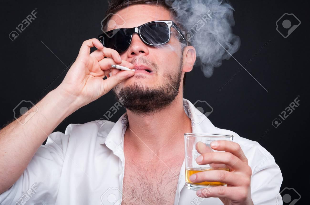 Closeu-up portrait of mafia killer smoking cigar and drinking alcohol on black background - 80505485
