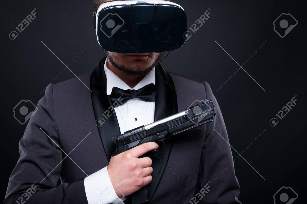 Mafia gangster in suit with vr glasses holding dangerous gun