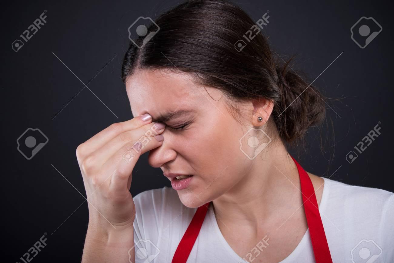 Closeup view of stressed female seller having headache or migraine - 87912360