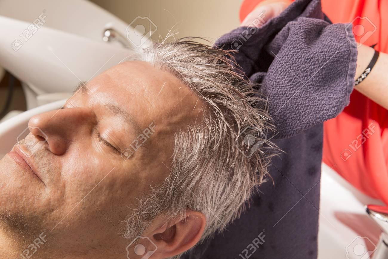Close up of face of man is getting a hairwash by a hairdresser, with relaxation. The beautician is making foam from shampoo - 51832339