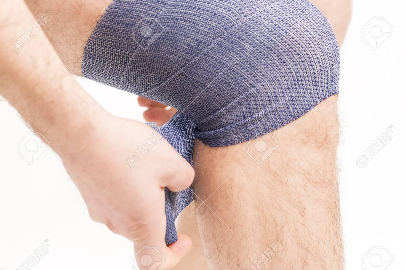 Man Putting Elastic Bandage On Knee Pain Health France Stock Photo