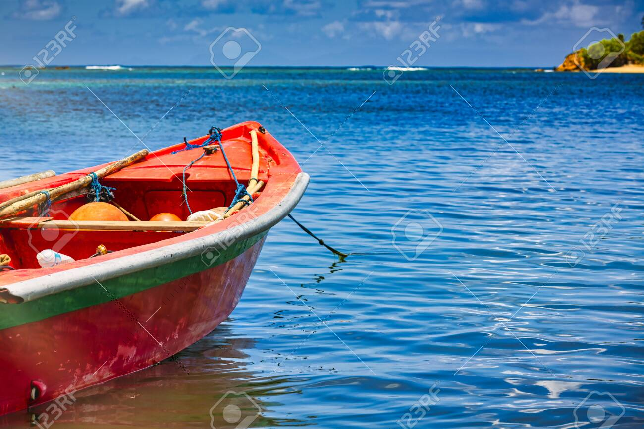 Small wooden colorful boat on crystal blue water ocean at gold