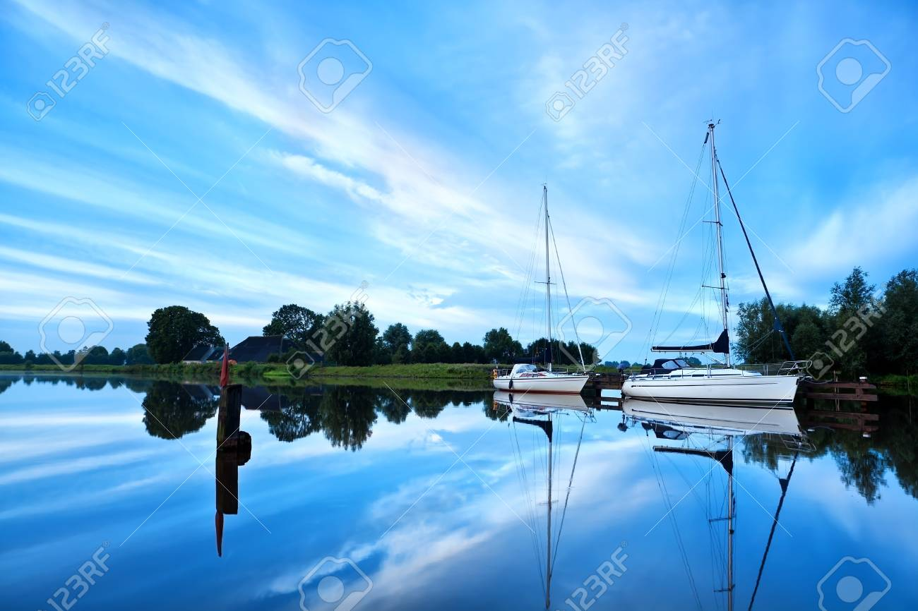 two yachts on river during calm morning with beautiful cloudscape Stock Photo - 19049458