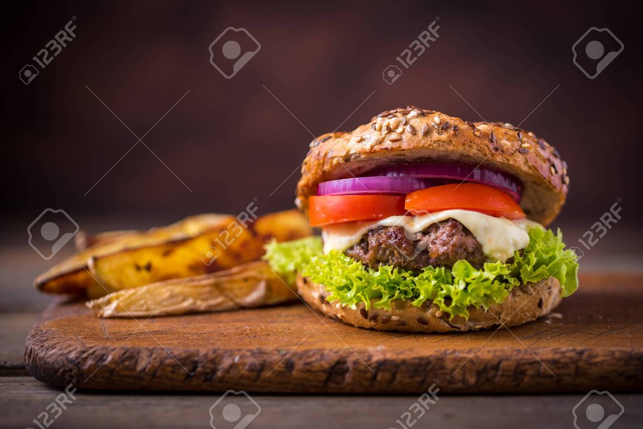 Home made hamburger with green salad and with american potatoes behind. Brown wooden background. - 121889883