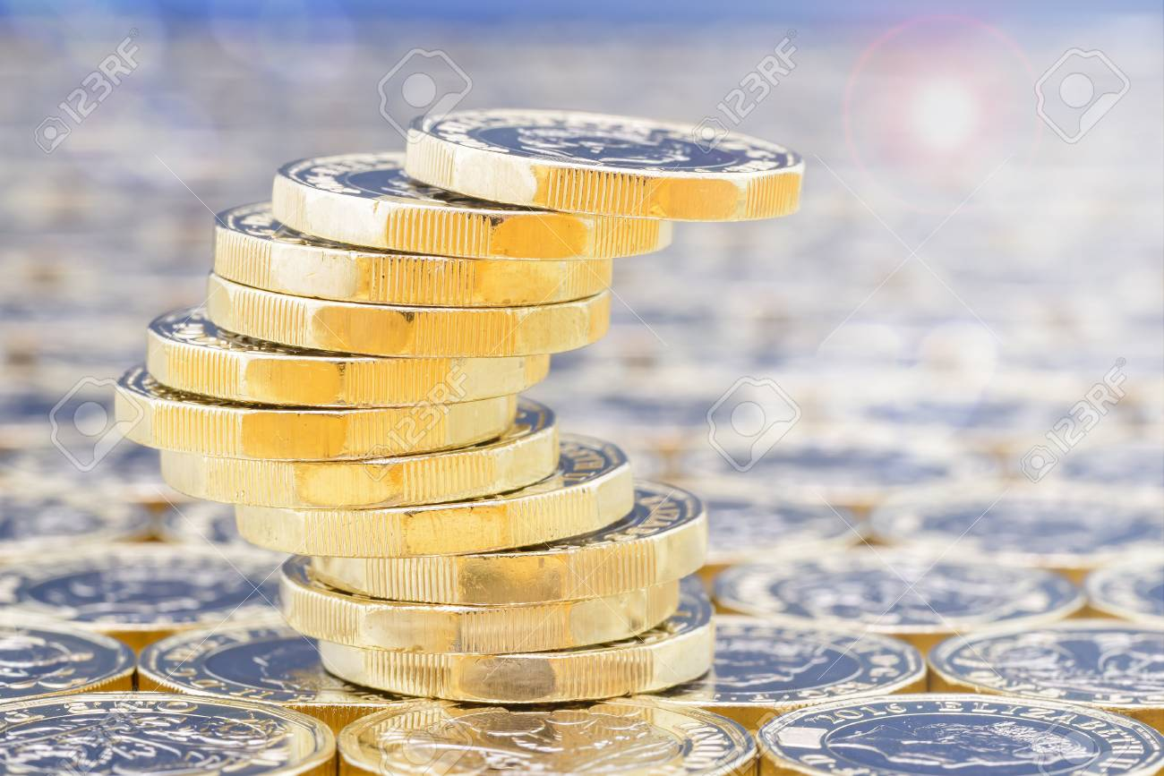 Golden coins with light effects. British pound coins in a precarious stack on a background of more money with lens flare and light filters. - 83413906