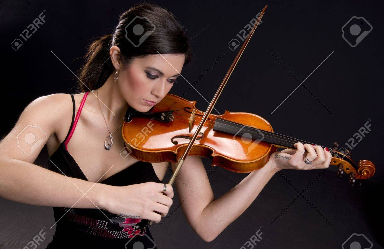 Beautiful Violinist looks at her instrument Stock Photo - 14669317