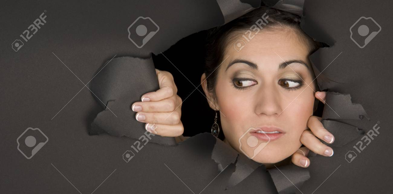 A beautiful and curious brunette peeks in through a hole Stock Photo - 15512231