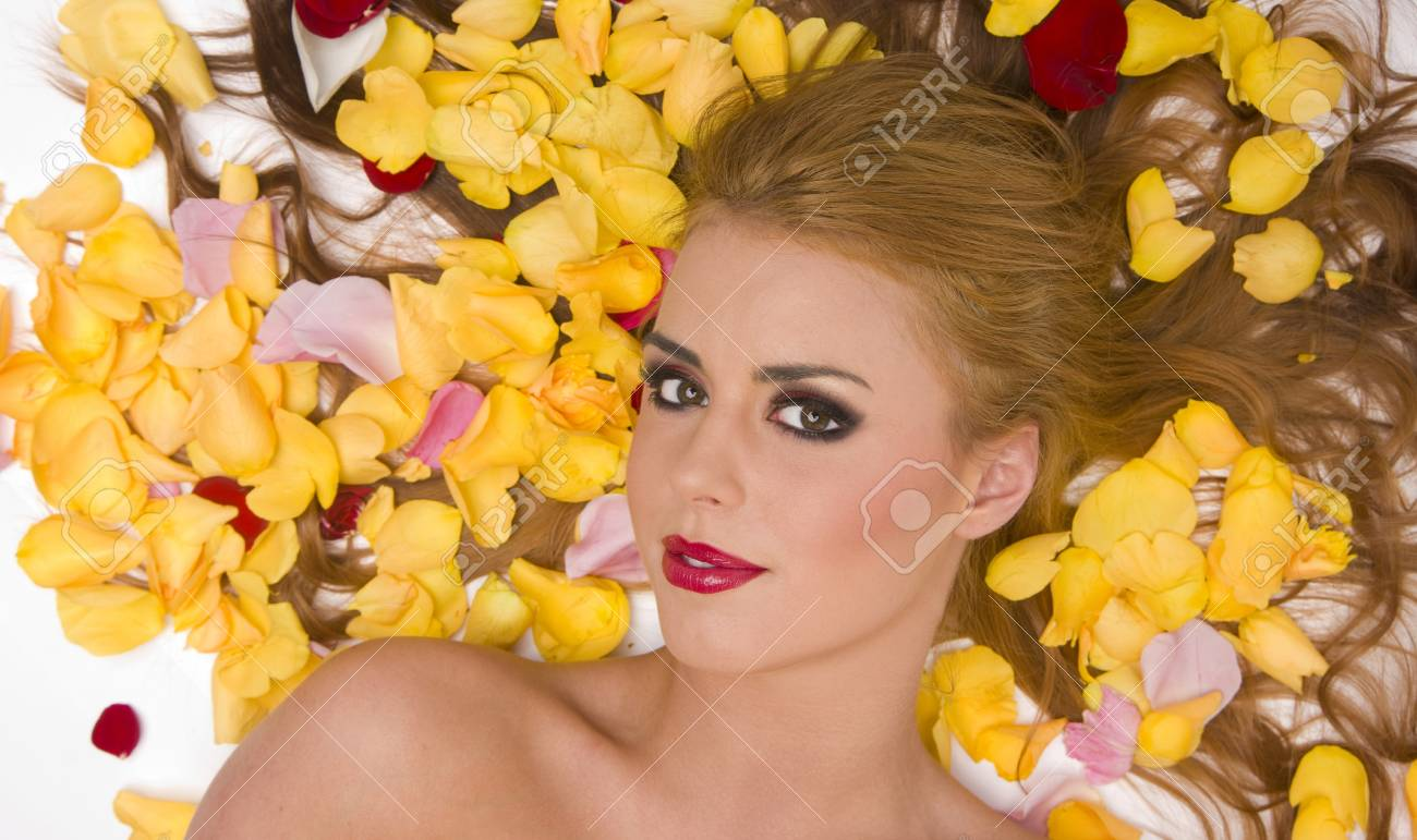 Beautiful woman lays in a pile of rose petals Stock Photo - 15512250