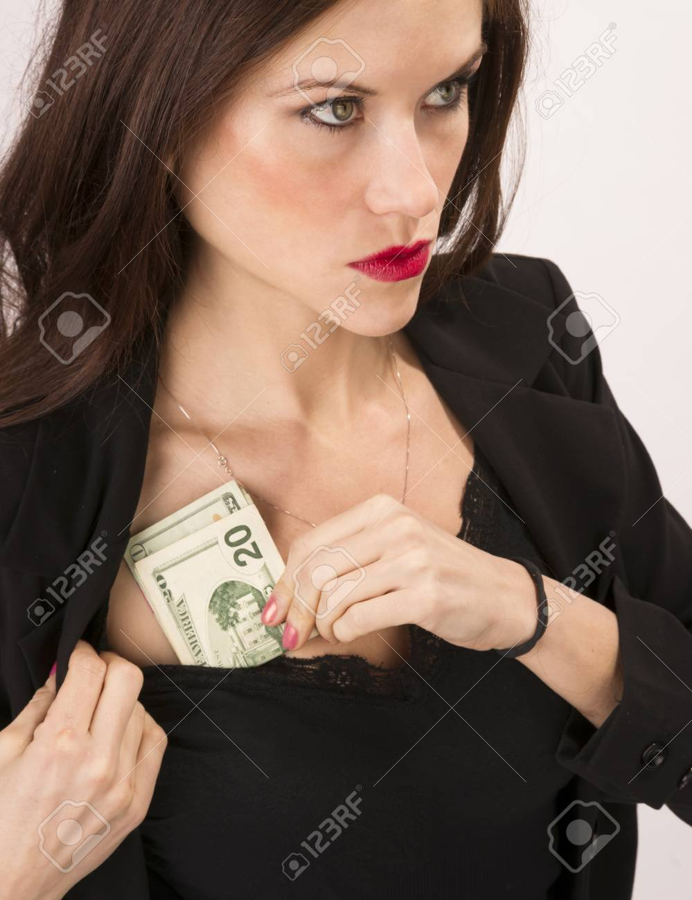 A good looking brunette woman stuffs money into her shirt Stock Photo - 23184442
