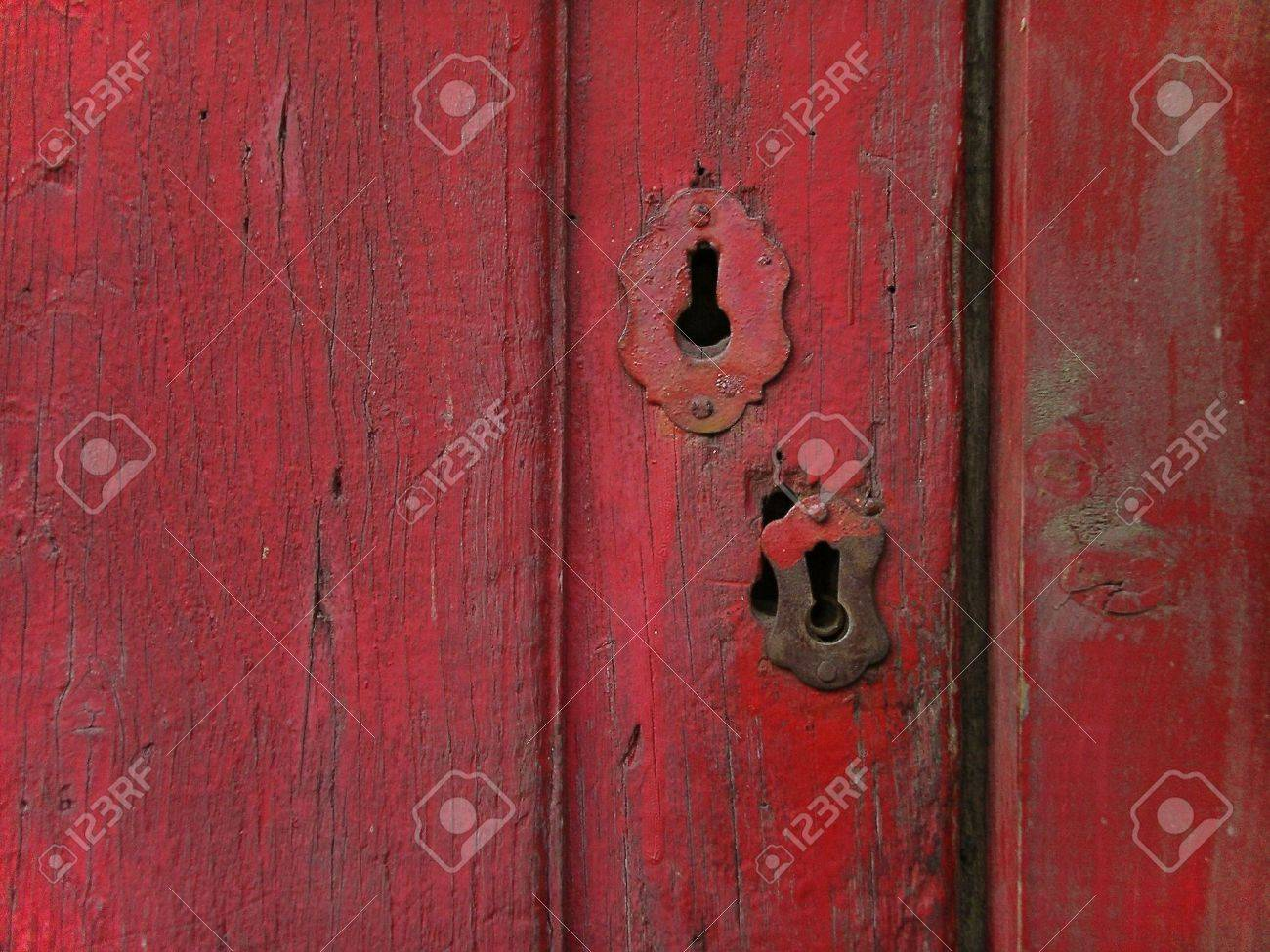 Rusty old wooden door painted in red, with metalic keyhole. Stock Photo - 2427116