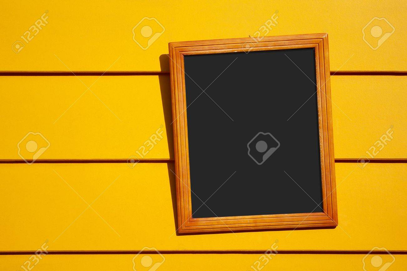 Empty blackboard with yellow frame hanged in a yellow wall Stock Photo - 3706547