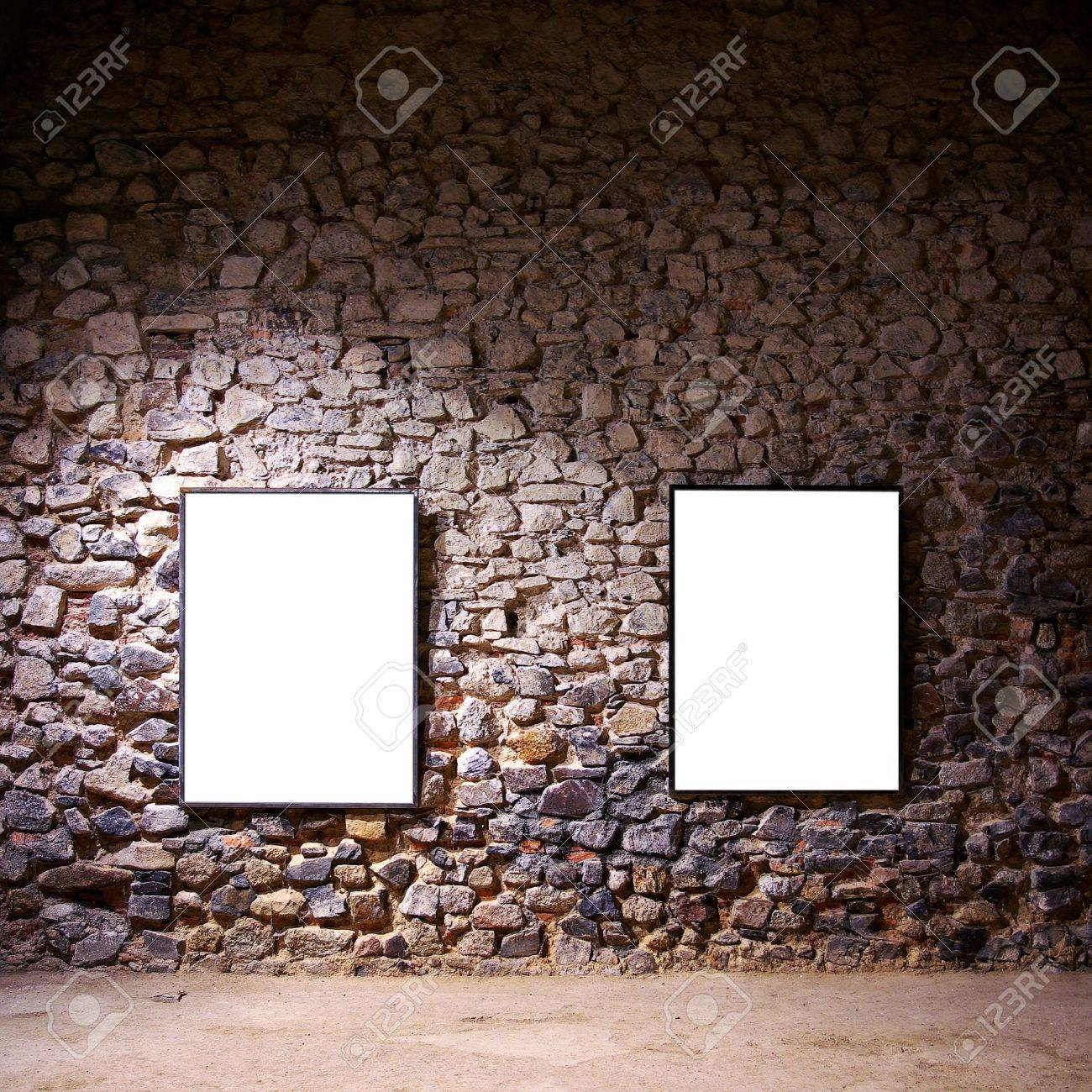 stock photo two empty frames attached to a stone wall in a gallery room