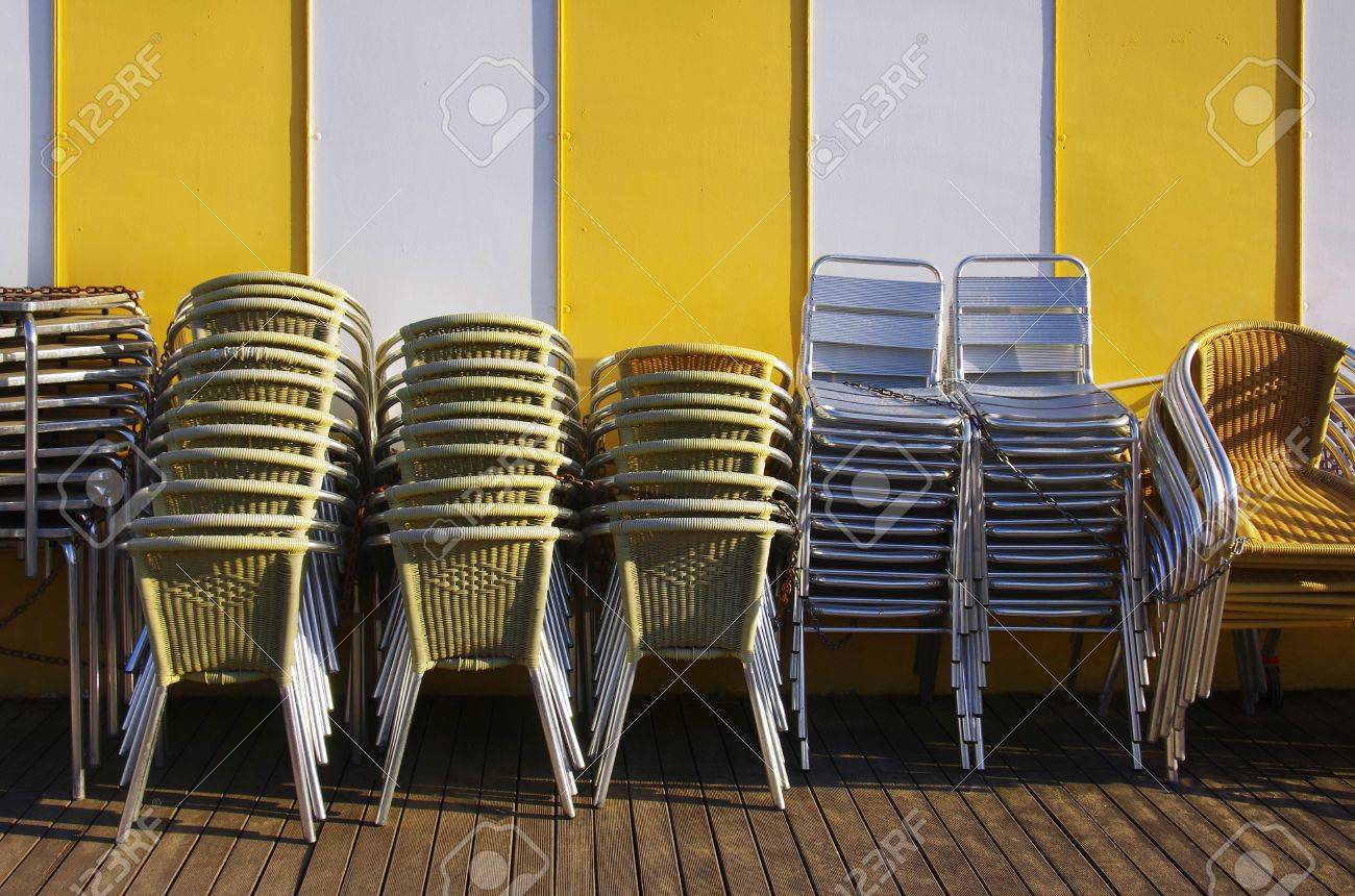 Groups Of Tables And Chairs Stacked And Chained Together Against A Yellow  Striped Wall Stock Photo