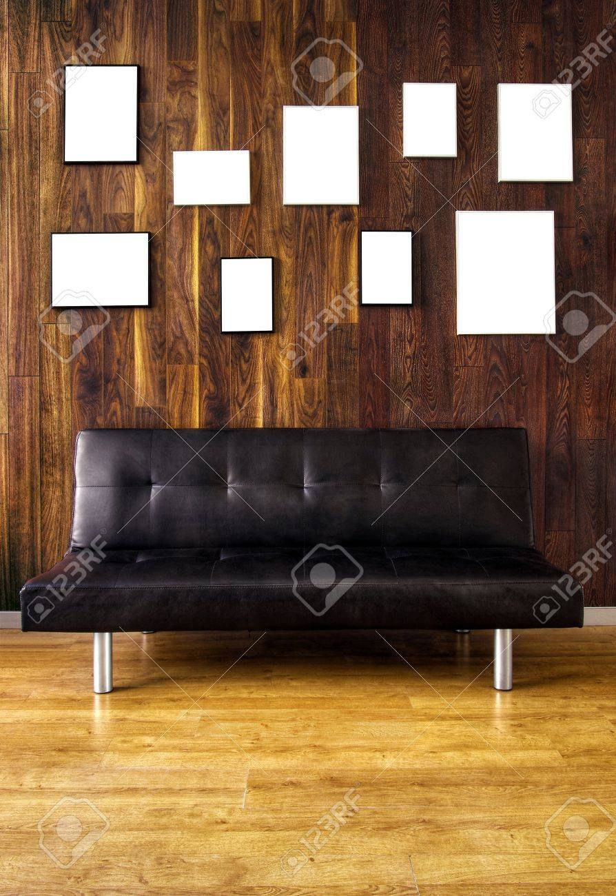 9fd3d190b69 A black leather couch against a wooden covered wall with many empty picture frames  Stock Photo