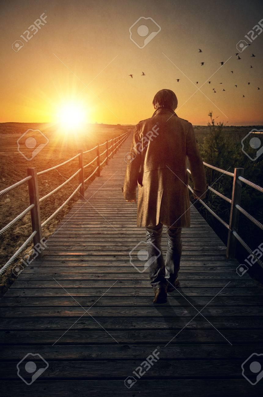 A man with long coat walking in a boardwalk into de sunset - 51832897