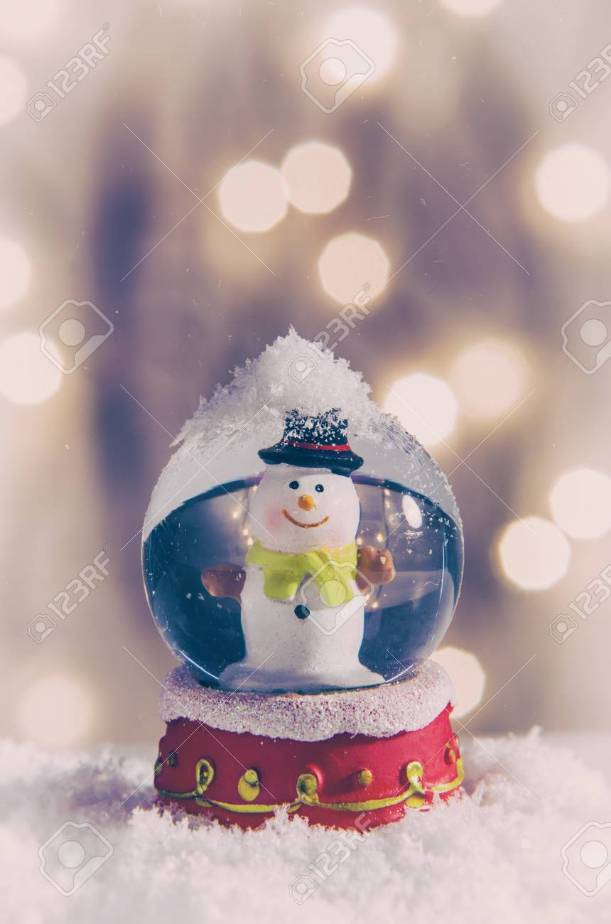 Vintage Christmas Snow Globes.Vintage Snow Globe With Snowman Over Christmas Lights Background