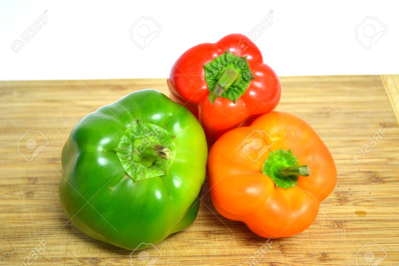 red orange and green peppers on wood cutting board isolated on white background close up Stock Photo - 12105688