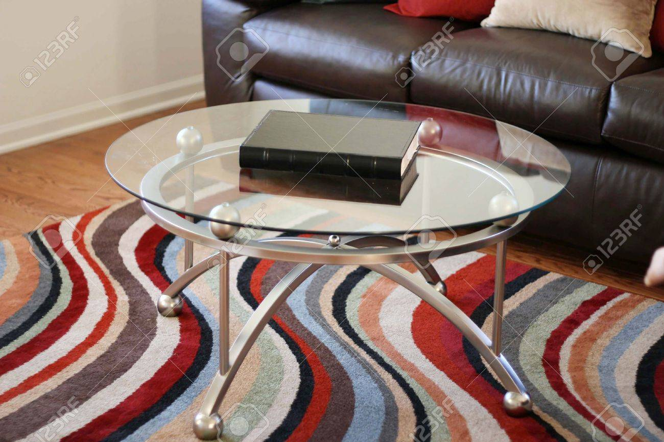 Glass Table On A Striped Rug Next To A Brown Leather Couch