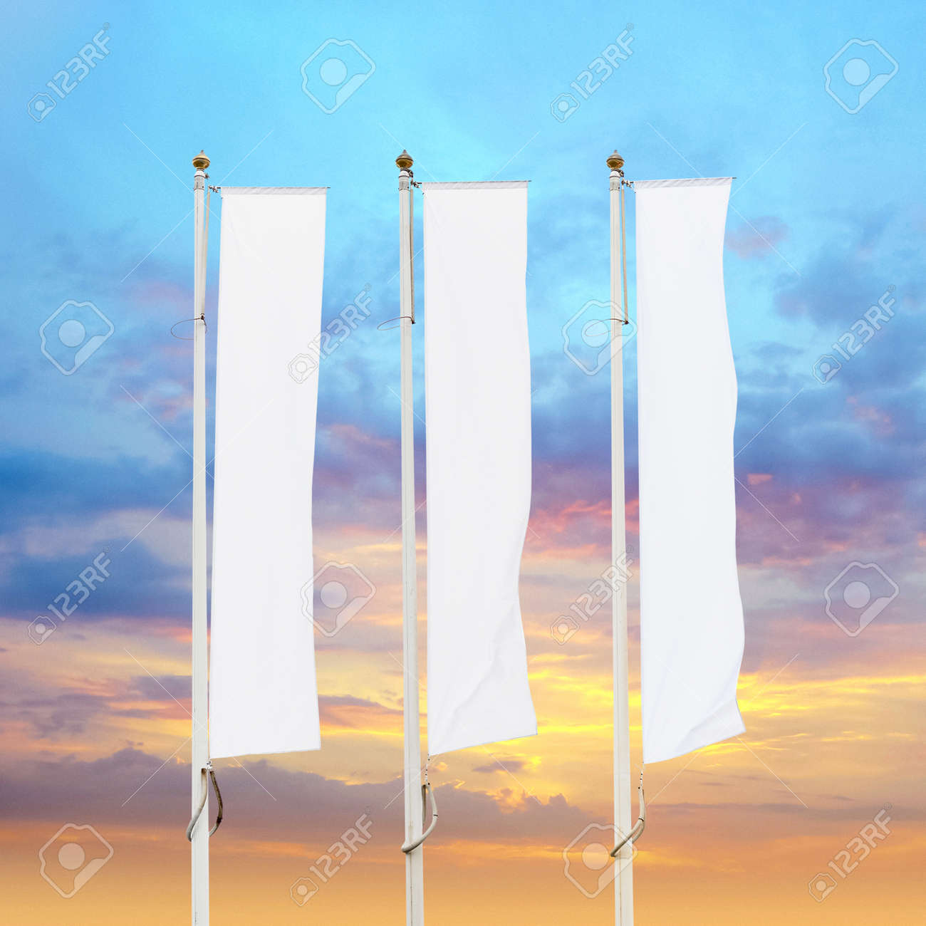 Three blank white corporate flags on flagpoles with sunset sky background, corporate flag mockup to ad logo, text or symbol, company identity flag template with copy space - 120653261