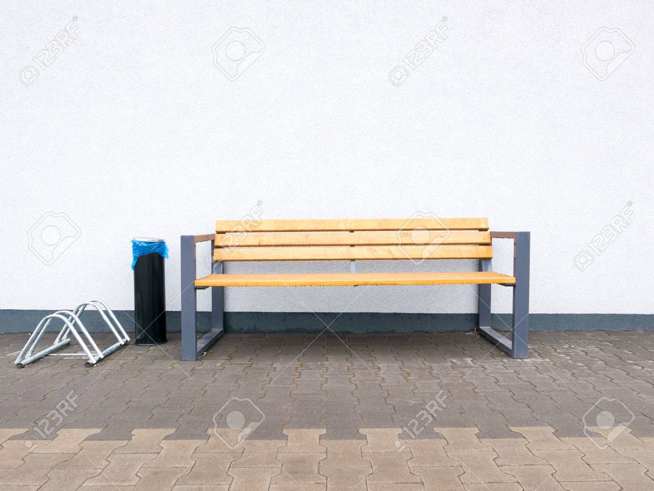 Empty modern outdoor bench and bike rack and industrial ashtray at wall background stock photo