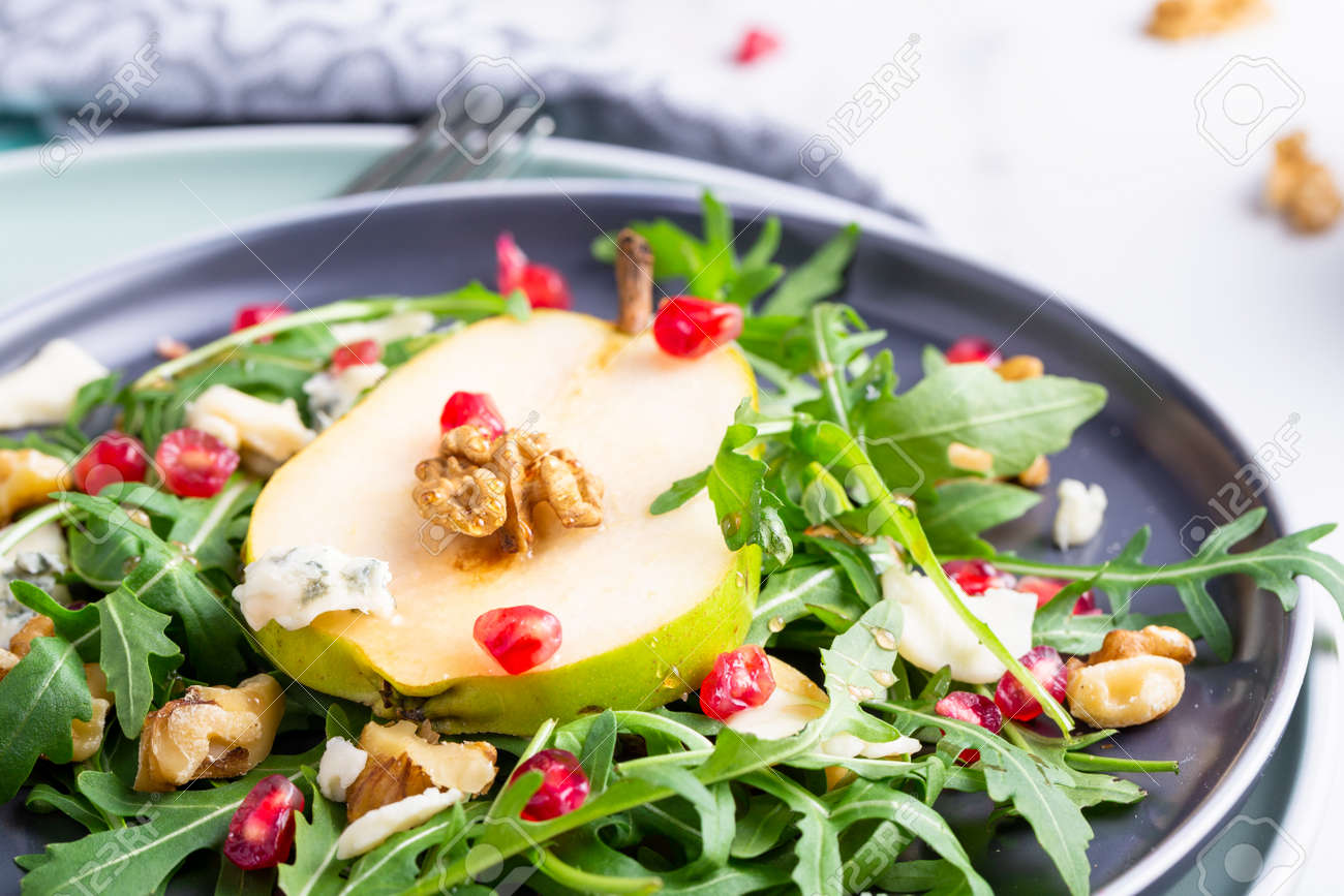 Fresh and healthy salad with arugula, gorgonzola cheese, pomegranate and pears. - 167761070