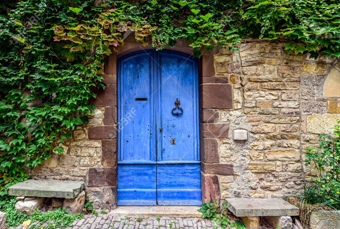 A blue and worn door with green ivy above on the stone walls of a small town in French countryside - 92543608