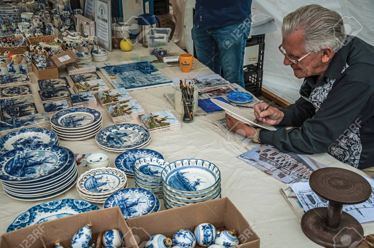 Skilled artisan hand-painting crockery in the region typical style at Gouda. Very popular day trip destination, is famous for its tasty Gouda cheese. - 99590707