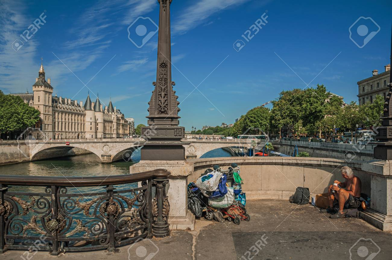 """Paris, France - July 08, 2017. Beggar on bridge over the Seine River with sunny blue sky in Paris. Known as the """"City of Light"""", it is one of the most impressive cultural centers in the world. Northern France. - 103206711"""