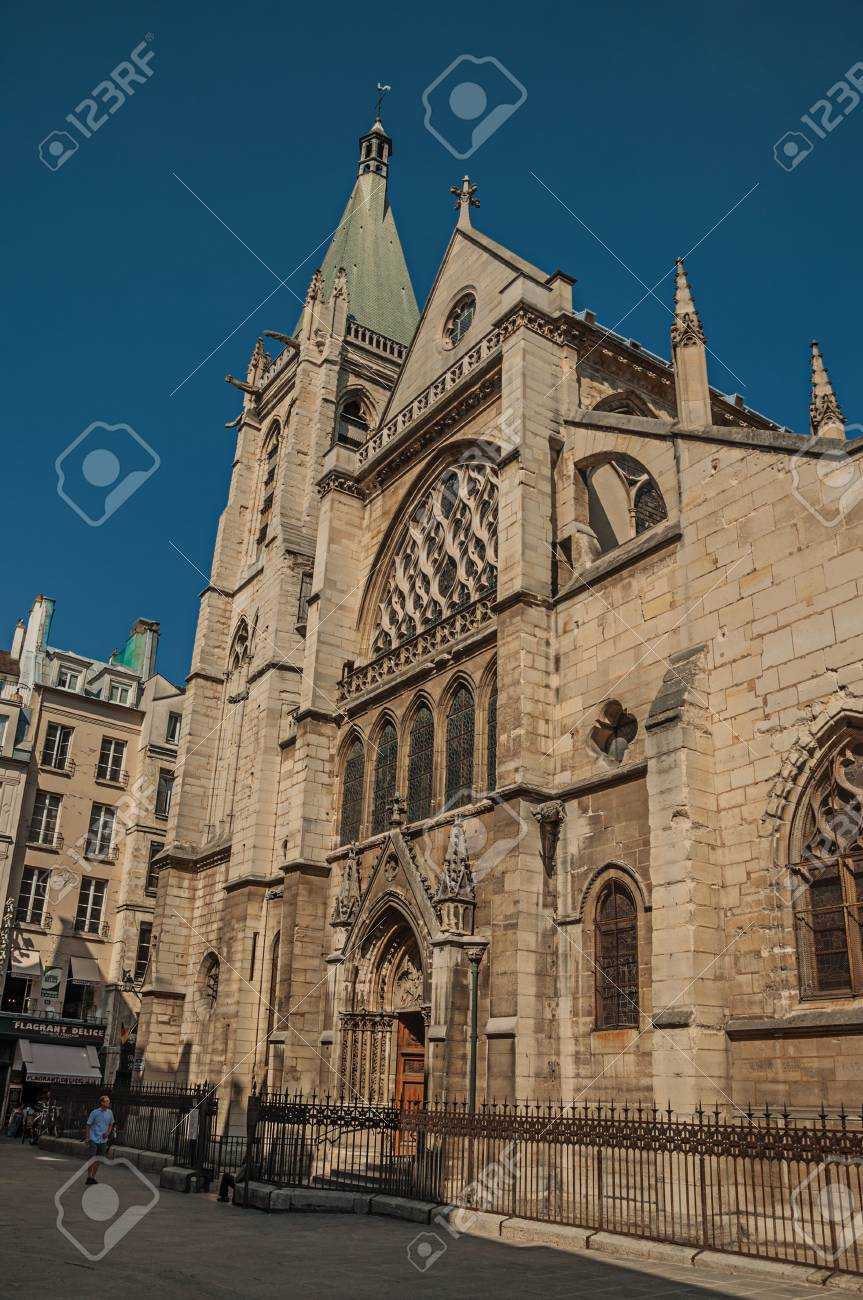 """Paris, France - July 08, 2017. People, gothic church on an alley and sunny blue sky in Paris. Known as the """"City of Light"""", it is one of the most impressive cultural centers in the world. Northern France. - 103272882"""