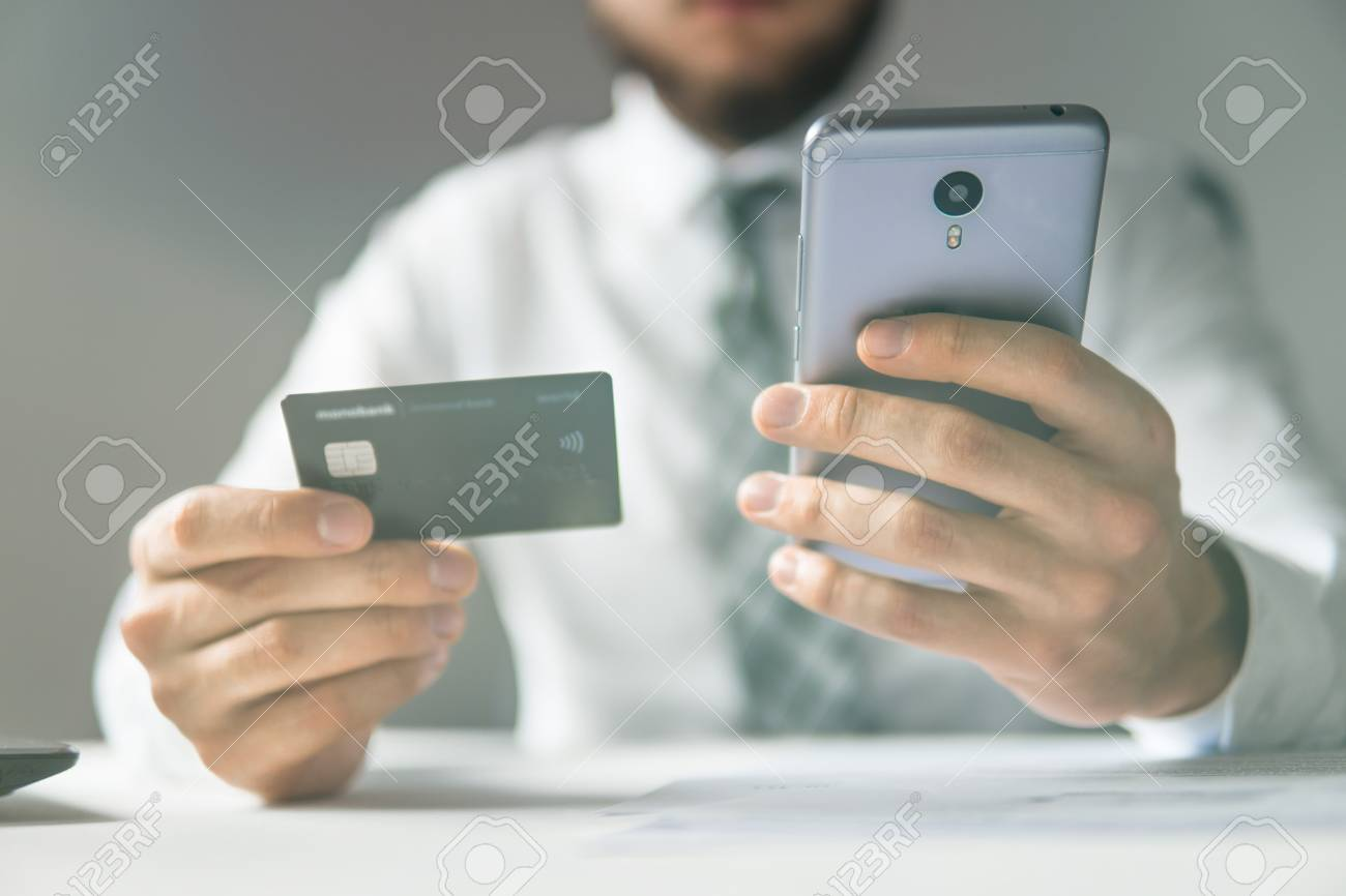 1a60f38684d Businessman uses credit card and a smartphone. Mobile phone. Online  payment. Shopping online