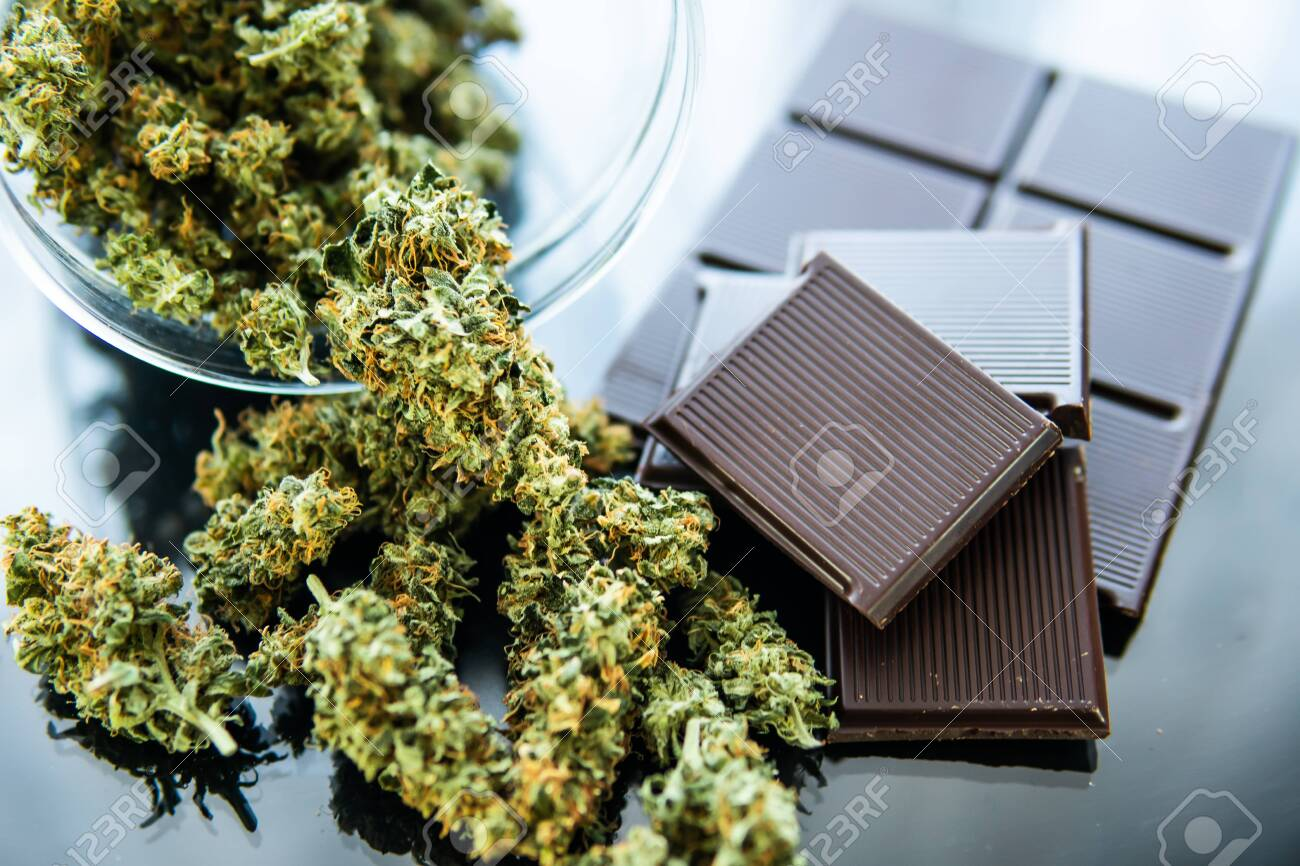 Concept of chocolate with cannabis herb CBD. Treatment of medical marijuana for use in food, black background. Chocolate with cannabis and buds of marijuana on the table. - 122401552
