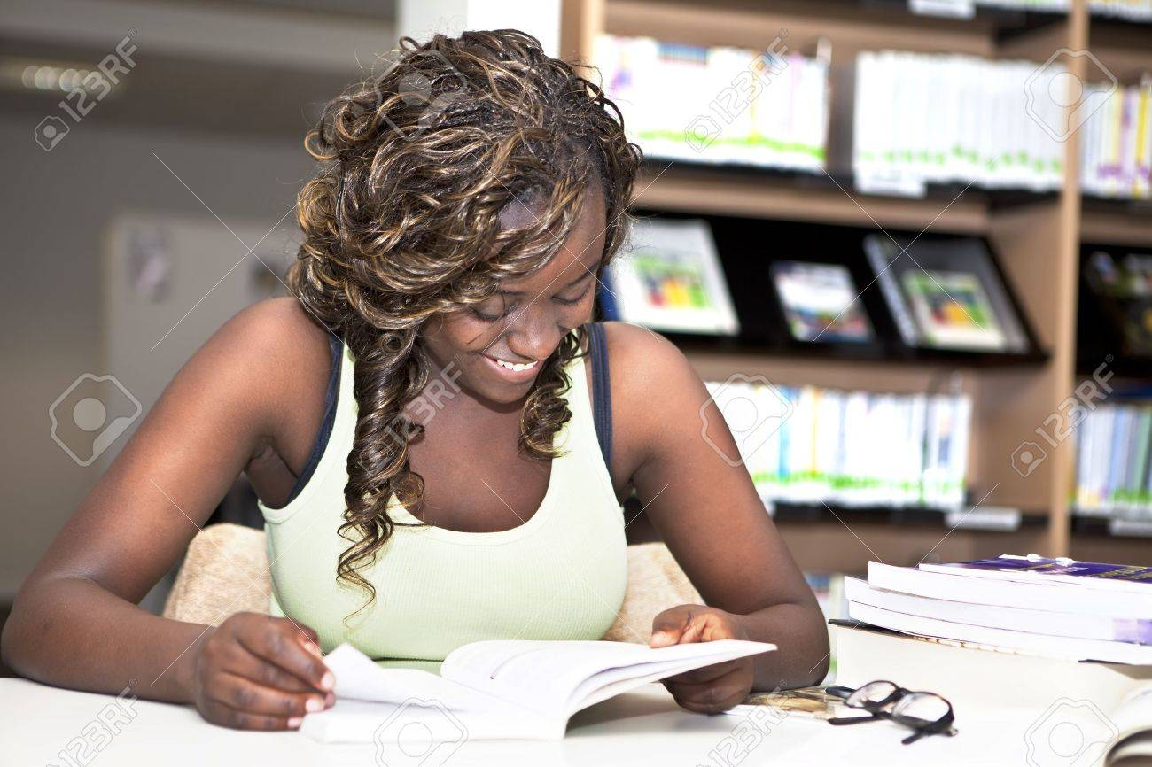 Pretty teenage black african college student girl smiling and reading a book in the library Stock Photo - 14460998