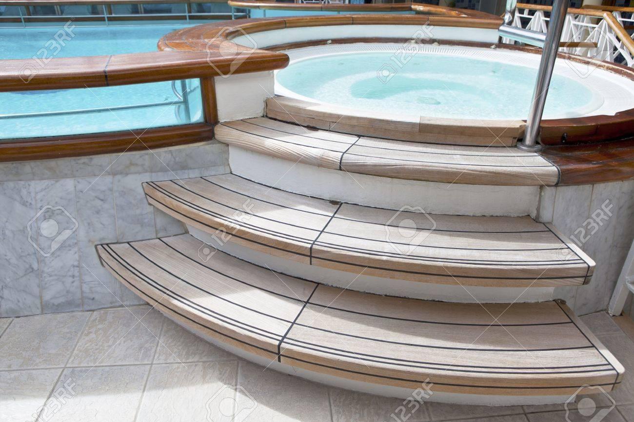 hidromasaje jacuzzi con escalones de madera y una piscina en la cubierta de un barco de
